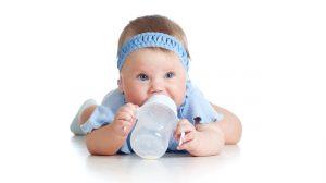 תינוקת שותה בקבוק חלב
